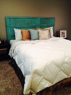 headboard made from old shutters painted antiqued and hung on the wall as