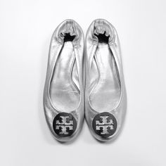 Silver Tory Burch Reva Flats Used silver Tory flats with scratches here and there and one of the heels is worn down a little. Size 7.5 but tag is warn off. Box not included Tory Burch Shoes Flats & Loafers
