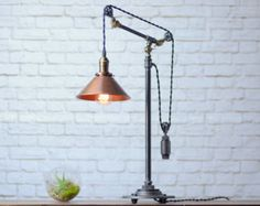 This industrial table lamp can be adjusted at two articulating fittings for a variety of heights and conformations.  A 60 watt filament bulb lights up an 8 inch aged copper shade for a warm ambient glow.  The table lamp is constructed from industrial black iron. The vintage bulbs are now carried at local hardware stores for easy replacement. Power is supplied by a retro braided cloth power cord. The high end antique brass socket features a vintage on/off key switch.  Dimensions:  Height ...