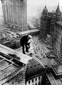 a brave and formally dressed photographer shooting the city from atop a skyscraper, mid-1920s