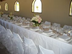 White chair covers and organza sashes with  beige table runner for hire