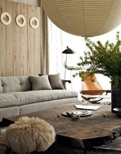 giant paper lantern, woodcut coffee table, grey down sofa, leather sling chair, wood paneled wall, fern, moroccan lamb pillow, #livingroom