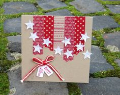 handmade Chrismas card ... kraft base with red and white adornments ... strips of red patterned washi tape hanging from the top ... punched and glittered stars .. red and white string with jewelry tag sentiment ... fun look!!