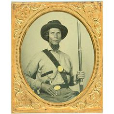 SUPERB DOUBLE ARMED WESTERN CONFEDERATE, 1/6th plate ambrotype in a full thermo plastic case. This Rebel appears to have Native-American blood. He wears a slouch hat and a battle short with dark stripes at the edges of the pockets. Across his chest is a tinted eagle plate on his cartridge box belt and he has a small oval US buckle that has been recycled from the Mexican War. He holds a model 1842 musket and has a large revolver in his belt. His dress is indicative of a Trans-Mississippi…