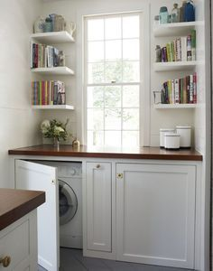 Laundry room idea. Conceal the washer dryer behind built in cabinet doors. Love the open shelves and dark wood counter top.