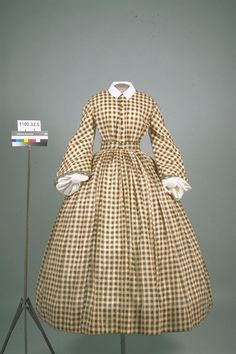 Checked semi-sheer dress. High gathered bodice, funnel sleeves, gathered skirt. Trim at sleeve opening, buttons on bodice front; shown with white collar and undersleeves. A BETHKE
