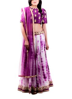 Dress to impress in this white and aubergine printed lehenga by Kirti J. The aubergine color choli is embellished with zari and mirror work. The high neck and the elbow length sleeves give the choli a smart and chic finish.