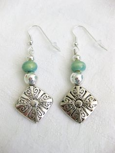 Large flat silver metal bead with detail, silver metal and glass sea foam green beads, on silver fish hook earrings. Earrings are about 1.5