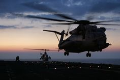 A really neat night shot of a CH-53 taking off from the deck of an Amphibious assault ship. An A-H1 Cobra gunship on deck in the back ground.