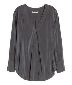 H&M. CONSCIOUS. Wide V-neck blouse in an airy weave with long sleeves with wide, buttoned cuffs and a rounded hem. The blouse is made partly from recycled polyester. Black.