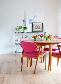 Cadeiras de madeira com estofado rosa e flores pela sala