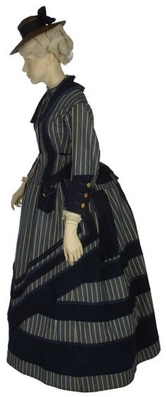Early 1870s dress designed for boating or seaside walking. A hemline just at the ankle indicates a garment intended for walking outdoors. The style of the dress has been inspired by the colors and stripes of sailors' uniforms. Despite its practical use, the ensemble still incorporates the details of fashionable dress, with an over skirt in front and a bustle worn underneath at the back, via V&A Museum.