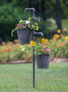 This double faucet garden stake gives the appearance that water could be running into the two plant holders hanging below. Made of weathered metal, this stake