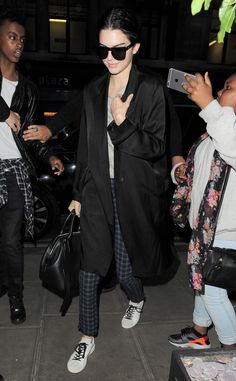 Kendall Jenner steps out in plaid pants, sneakers, a long black coat, grey top, a black top handle bag and sunglasses.