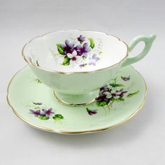Heathcote bone china tea cup and saucer, pale green with violets. Gold trimming on cup and saucer edges. Excellent condition (see photos). Markings read: Bone China Heathcote Made in England Please bear in mind that these are vintage items and there may be small imperfections from
