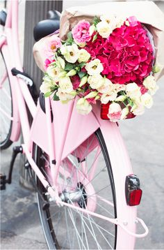 Beautiful flowers on the back of a pink bike
