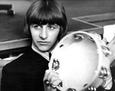 A mop-topped Ringo Starr poses for the camera while playing his tambourine.