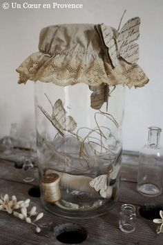 Papieren vlinders in een glazen potje.