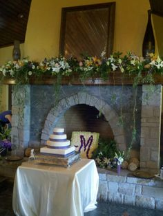 Beautiful Fireplace Mantel Floral Arrangement with Draping Greenery and Square Floral Initial in Fireplace. http://www.busseysflorist.com/wedding-flowers/