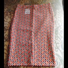 NWT Zara mid length stretchy fitted pencil skirt New with Tags Zara mid length 24 inches long fitted stretchy skirt.  Elastic at the waist.  Small slit at back.  It is ivory black and orange geometric design, very complementary Zara Skirts Pencil
