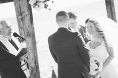 Bride smiles at her groom during their beach wedding ceremony at Westhampton Bath & Tennis in Westhampton, NY. Captured by NYC wedding photo...
