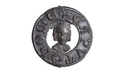 Pilgrim badge from the shrine of St Thomas Becket at Canterbury Cathedral. This badge has a circular frame bearing the words 'CAPVT THOME', meaning 'Thomas's head'. In the centre is a depiction of the head-shaped reliquary bust that held the remains of Becket's skull.