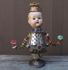 Found Objects Assemblage Buttons, tin, baby doll face, tea cup, lights. No artist listed. No inspiration. Public.