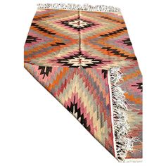 Vintage handmade decorative kilim with lovely pink accents. This piece is approximately 60 years old. Very fine quality. Professionally cleaned and ready to use in your home.