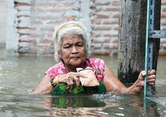 2011 floods in Thailand: An elderly Thai resident wades through water in a flooded street in Pak Kret district in Nonthaburi province, on the outskirts of Bangkok
