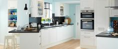 Greenwich Shaker White Kitchen Range | Kitchen Families | Howdens Joinery, with big dark knobs for doors and handles.