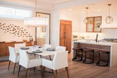 Designer Valerie Saunders of Serendipite paired sleek white surfaces with warm wooden accents to create a calm, contemporary kitchen. Pops of blue nod to the home's coastal location.
