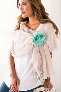 Creating effortless elegance is as easy as gathering a pompomed scarf around your shoulders and securing it with a flower pin.