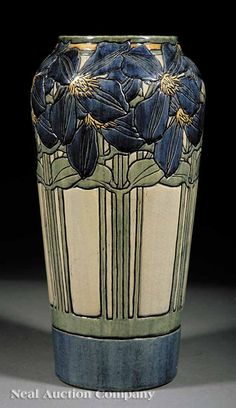A Fine Newcomb College Art Pottery High Glaze Vase, 1904, decorated by Marie de Hoa LeBlanc, with an incised design of jackmanii climbing clematis in blue, green, and yellow underglaze, the base marked with Newcomb cipher, decorators mark, Joseph Meyers potters mark, Q for buff clay body and reg. no. VV19, height 13 in., diameter 6 1/2 in
