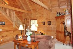 Up one flight of stairs, you will find this living room featuring 25 vaulted ceiling with exposed beams and high triangle windows. Timber Frame Home Plans, Timber Frame Homes, Log Cabins For Sale, Cabins In The Woods, Cabin Homes, Log Homes, Parts Of Stairs, Wooden Stairs, Wooden Cabins