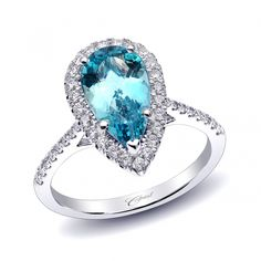 COAST DIAMOND ~ This flattering ring features a pear shaped 2.12CT aquamarine surrounded by a graceful diamond halo. Diamonds decorate the shoulders of the ring. Set in 14k white gold.