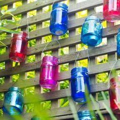 Colorful tealight lanterns hanging from trellis