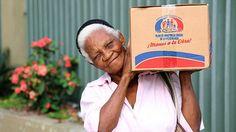 Esta pobre mujer sonrie a la camara que la capta cargando una caja conteniendo alimentos suficientes para hacer la cena de navidad, quizas uno de los pocos bocados que podra probar durante el ano que termina antes de acomodarse en su camastro. Aun asi, el Latinobarometro dice que el Dominicano es un pueblo feliz.