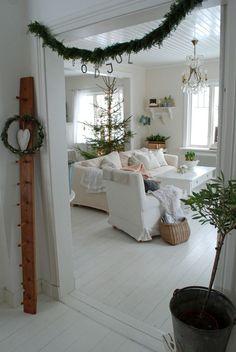 weiße Bezüge für die Wohnzimmermöbel und grüne Girlanden