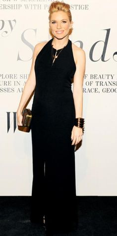 Look of the Day › February 15, 2012 WHAT SHE WORE Sienna Miller arrived for The Ever Changing Face of Beauty's opening ceremony in a Boss Black halter gown, tiered necklaces, a box clutch and wide bangle. WHY WE LOVE IT The mom-to-be set off her sleek column with bronze accessories and her natural glow
