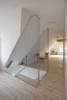 Fohn House Staircase with Blue Floor to Ceiling Cable Wire Railings and Gold Fastenings.