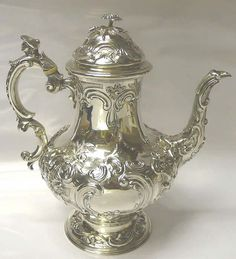 OnlineGalleries.com - Antique Silver Coffee Pot A handsome antique sterling silver coffee pot of baluster form on a pedestal base. With deeply chased decoration of flowers and leaves and the head of a young man on top of the handle. On the lid there is a pretty flower finial. Contains 1650 ml. Weight 1167 grams, 37.5 troy ounces. Height 27 cms. Spread 26 cms. London 1840. Maker Barnard Brothers.
