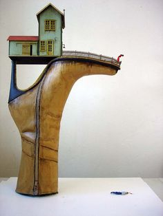 """The House on the Heel"". Mixed media on fiberglass cast shoe Costa Magarakis is a fine artist working with different kinds of mediums and specializing in sculptures. His work can be expressed as a gothic wonderland illuminating the gray area between truths and lies."