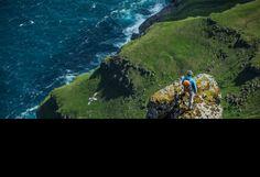 Mann steht auf der Spitze eines Felsen in den Bergen, Färöer Inseln