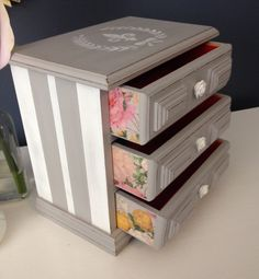 """$48. Gray and White Shabby Chic Jewelry Box by CocoandQuinnVintage. Music Jbox painted light gray, stenciled white, lightly distressed, sealed w/soft wax. Drawer sides decoupaged shabby chic floral print. Handles replaced w/white rose knobs. Drawers lined with a red velveteen. Music plays when the bottom drawer is opened. Measurements: 7 1/2"""" H x 7 1/2"""" W x 4 3/4"""" D. Insides thoroughly cleaned or replaced."""