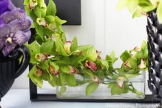 love the way these green orchids lay across the rectangular glass vase