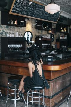 Summer style. Black dress. Lace heels. Chain strap bag. Rustic Bar Interior.