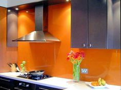 I love this idea of painting the back-splash orange & covering it in glass. Easy to clean but eye-popping!