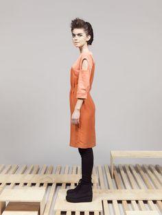 Gateway Dress bij Femke Agema - Knielange jurk in soepele viscose met ribfluweel Jurk met speelse openingen op de bovenkant van de driekwart mouw in zalmkleur. Blinde rits in de zijnaad, split middenachter