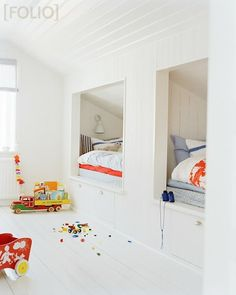 built in beds, sloped ceiling, attic play room, day beds, all white room, plank wood floors, cozy reading nook