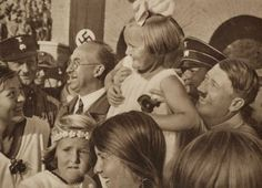 Adolf Hitler smiles as he carries Magda Goebbels' daughter during an event in Germany, 1936. [640 x 462]
